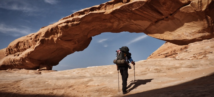 Author walking towards the great rock arch at Jebel Kharazeh, Jordan